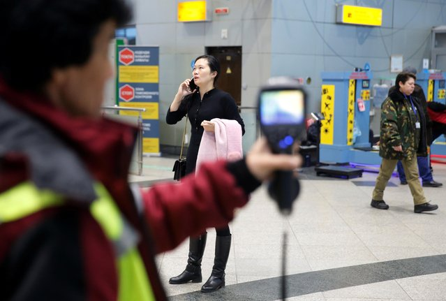 Kazakh sanitary-epidemiological service worker uses a thermal scanner to detect travellers from China who may have symptoms possibly connected with the previously unknown coronavirus, at Almaty International Airport, Kazakhstan January 21, 2020. Airports in the United States, Australia and across Asia have begun extra screening for passengers from Wuhan. (Photo by Pavel Mikheyev/Reuters)