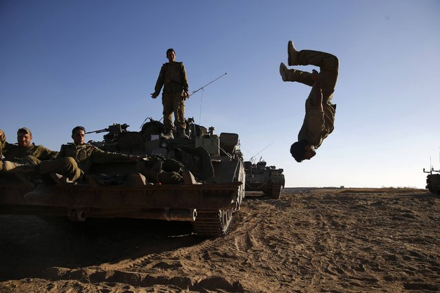 """An Israeli soldier somersaults from an armoured personnel carrier (APC) stationed on a field outside the central Gaza Strip July 11, 2014. Prime Minister Benjamin Netanyahu said on Friday Israel has attacked more than 1,000 targets during a four-day-old offensive against Gaza militants and that """"there are still more to go"""". (Photo by Baz Ratner/Reuters)"""