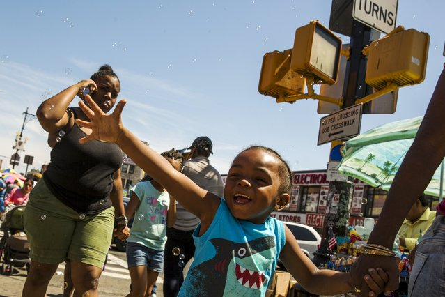 A young child reaches out to touch bubbles being blown on the street in a region of the South Bronx that has seen a deadly outbreak of Legionnaires' disease in New York August 7, 2015. (Photo by Lucas Jackson/Reuters)