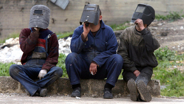 Palestinian welders watch the partial eclipse of the sun using visors during a break from work in the West Bank city of Ramallah, 29 March 2006. The eclipse, caused by the moon blotting out the sun, begun on the northeastern tip of Brazil, racing across the Atlantic Ocean and over northwest Africa and parts of the Middle East and Turkey before covering Georgia and Central Asia. (Photo by Jamal Aruri/AFP Photo)