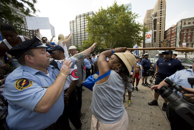 Police try to stop a woman wielding a cane from hitting a woman supporting Israel in its war with Hamas, not pictured, during a rally at John F. Kennedy Plaza, also known as Love Park, in Philadelphia on Wednesday, July 23, 2014. (Photo by AP Photo)