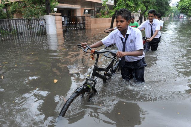 Indian school boys wade along a flooded street following heavy rains in Ahmedabad on July 24, 2014. The Indian Metrological Department has predicted heavy rains for the next 24 hours across Gujarat state. (Photo by Sam Panthaky/AFP Photo)