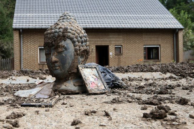 A statue of Buddha and storm debris are covered with mud outside a flooded house after heavy rains hit the town of Ittre July 30, 2014. (Photo by Francois Lenoir/Reuters)