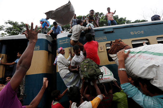 People climb to board an overcrowded passenger train as they travel home to celebrate Eid al-Fitr festival, which marks the end of the Muslim holy fasting month of Ramadan, at a railway station in Dhaka, Bangladesh, July 5, 2016. (Photo by Adnan Abidi/Reuters)