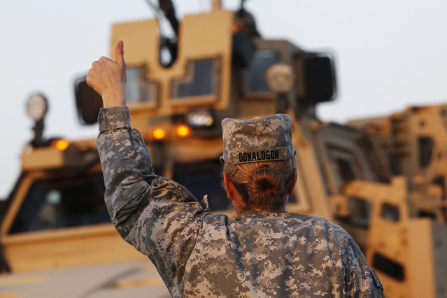 U.S. Army convoys are given the thumbs up from a fellow soldier after crossing into Kuwait during the last convoy out of Iraq December 18, 2011. (Photo by Shannon Stapleton/Reuters)