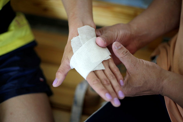 A coach wraps bandage on the hand of Mongolia's Olympic wrestler Battsetseg Soronzonbold during a daily training session at the Mongolia Women's National Wrestling Team training centre in Bayanzurkh district of Ulaanbaatar, Mongolia, July 1, 2016. (Photo by Jason Lee/Reuters)