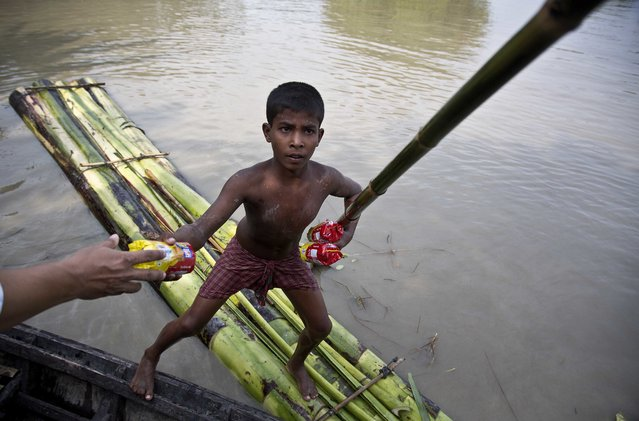 A flood affected boy on a makeshift banana raft collects biscuit packets distributed by a government official from a boat in Pokoria village, east of Gauhati, north eastern Assam state, India, Monday, August 14, 2017. Heavy monsoon rains have unleashed landslides and floods that killed dozens of people in recent days and displaced millions more across northern India, southern Nepal and Bangladesh. (Photo by Anupam Nath/AP Photo)