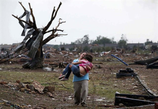 Second Place, Domestic News. Photo by Sue Ogrocki of the Associated Press:  LaTisha Garcia carries her 8-year-old daughter, Jazmin Rodriguez, near Plaza Towers Elementary School after a massive tornado carved its way through Moore, Okla., leaving little of the school and neighborhood. (Photo by Sue Ogrocki)