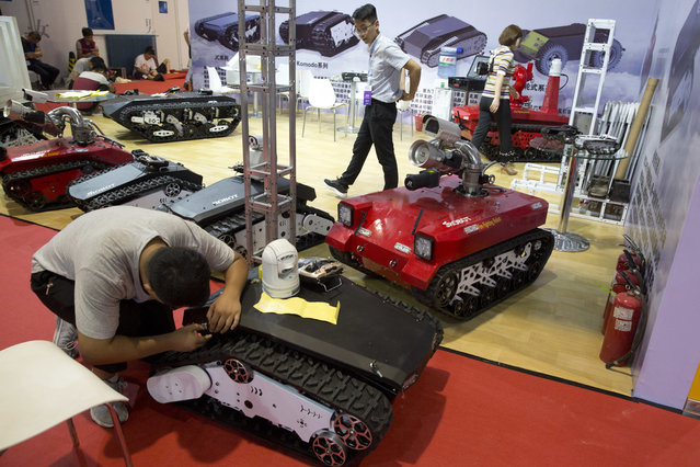 Tracked autonomous vehicles are prepared a day before the opening of the World Robot Conference held in Beijing, China, Tuesday, August 22, 2017. (Photo by Ng Han Guan/AP Photo)
