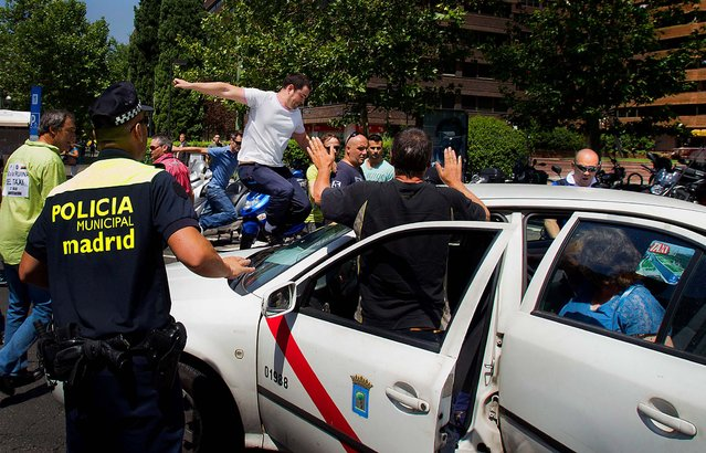 A taxi is attacked by other taxi drivers during a demonstration in Madrid, Spain on July 27, 2012.The taxi drivers are protesting the planned deregulation of the taxi sector. (Photo by Paul White/Associated Press)