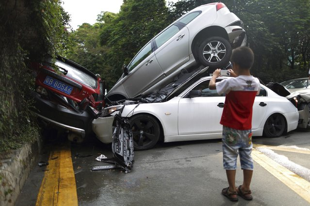 A boy takes a picture of a car crash in Shenzhen, Guangdong province, August 4, 2014. Two passengers were sent to hospital but no death was reported as a result of the accident, according to local media. (Photo by Reuters/Stringer)