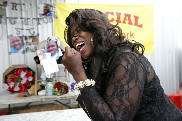 Stephanie McDee, who said she is a local blues singer, sings a song and protests at a makeshift memorial for Alton Sterling, outside a convenience store in Baton Rouge, La., Wednesday, July 6, 2016.   Sterling was shot and killed by Baton Rouge police outside the store where he was selling CDs. (Photo by Gerald Herbert/AP Photo)