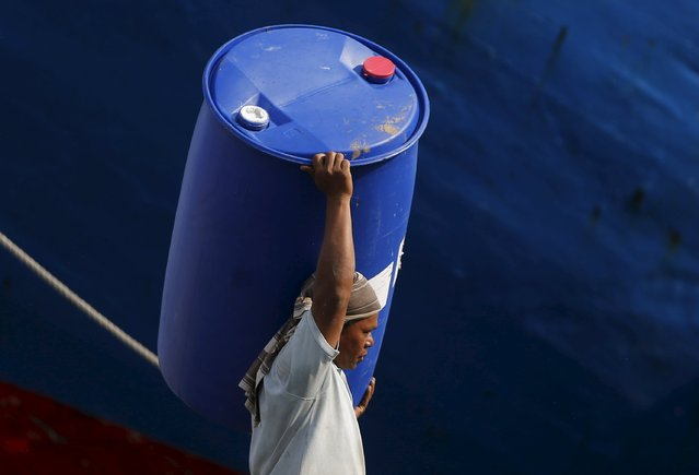 A worker carries a plastic container at Sunda Kelapa harbour in Jakarta, August 26, 2015. Bank Indonesia expects economic growth this year to slow to 4.7-5.1 percent from its previous estimate of 5-5.4 percent, central bank governor Agus Martowardojo said on Tuesday. (Photo by Reuters/Beawiharta)