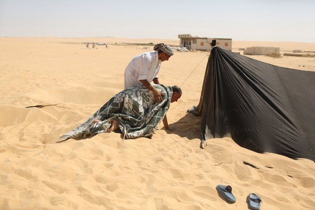 A worker helps a patient covered with a blanket to go to a sauna-like tent after he was removed from the hot sands where he was buried in Siwa, Egypt, August 12, 2015. (Photo by Asmaa Waguih/Reuters)