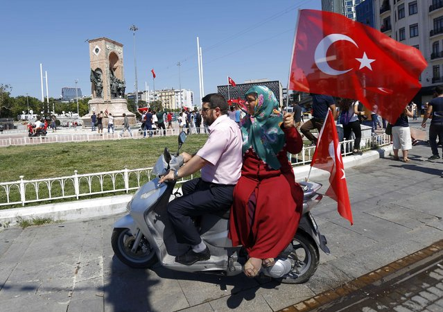 A woman holds a Turkish flag as she sits on a scooter near the Taksim Square in Istanbul, Turkey, July 16, 2016. (Photo by Murad Sezer/Reuters)