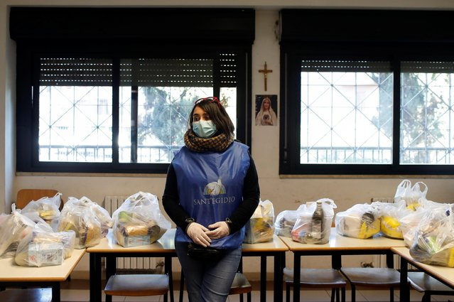 A volunteer wearing protective face mask and gloves stands next to bags during the food distribution organized by the Sant'Egidio Community at San Gaudenzio parish during the lockdown to prevent the spread of coronavirus disease (COVID-19), in Rome, Italy, March 23, 2020. (Photo by Yara Nardi/Reuters)
