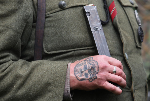 A WWII re-enactor dressed as a German soldier sports an SS Death's Head tattoo as he takes part in a mock battle as part of the two-day Maiden Newton At War 1940s re-enactment weekend in Maiden Newton, near Dorchester, England, on June 23, 2012. The quiet Dorset village of Newton Maiden was seen as a strategic hub during the Second World War and was heavily fortified against a threatened German invasion. It later saw hundreds of American servicemen quartered in the area before the D Day landings. To celebrate the village's wartime past, the biennial event, which started in 2008, has grown into one of the biggest re-enactments in the country and this year featured one of the largest convoys of Second World War vehicles seen in Dorset since D Day in 1944. (Photo by Matt Cardy)