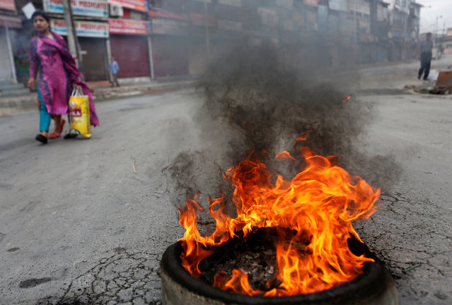 A girl walks past a burning tyre set afire by protesters during a curfew in Srinagar, India on July 18, 2016. (Photo by Danish Ismail/Reuters)