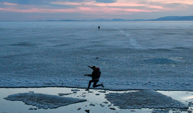 A teenager jumps from floe to floe during an ice drift in Amur Bay in the far eastern city of Vladivostok, Russia on March 22, 2020. (Photo by Yuri Maltsev/Reuters)
