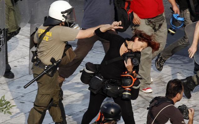 A riot policeman punches Greek photojournalist Tatiana Bolari during a demonstration in Athens' Syntagma (Constitution) square October 5, 2011. Police officers attacked several members of the press covering  protests, injuring at least two members of the media. (Photo by Yannis Behrakis/Reuters)