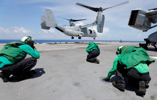 Crewmen brace themselves from the propeller wash of a Marine Corps MV-22B Osprey departing the aboard the USS Kearsarge as U.S. military continues to evacuate from the U.S. Virgin Islands in advance of Hurricane Maria, in the Caribbean Sea near the islands September 18, 2017. (Photo by Jonathan Drake/Reuters)