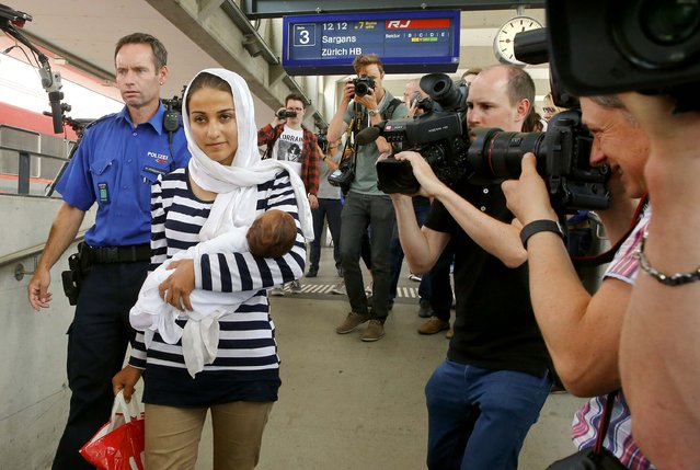 A Swiss police officer accompanies a migrant from Syria carrying her baby, as media takes pictures upon her arrival at the railway station in the north-eastern Swiss town of Buchs September 1, 2015. (Photo by Arnd Wiegmann/Reuters)