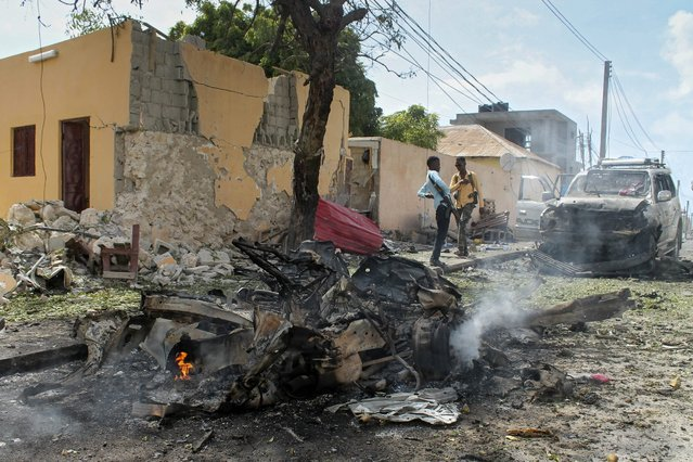 Somali security officers gather at the scene of a car bomb attack at the base for the African Union forces in Mogadishu, Somalia, 26 July 2016. Media reports say at least 10 people, including the security guards at the base which is located at Mogadishu's airport, have been killed after two car bombs exploded at the base. Somalia's Islamist militant group al-Shabab has claimed responsibility for the latest attack. (Photo by Said Yusuf Warsame/EPA)