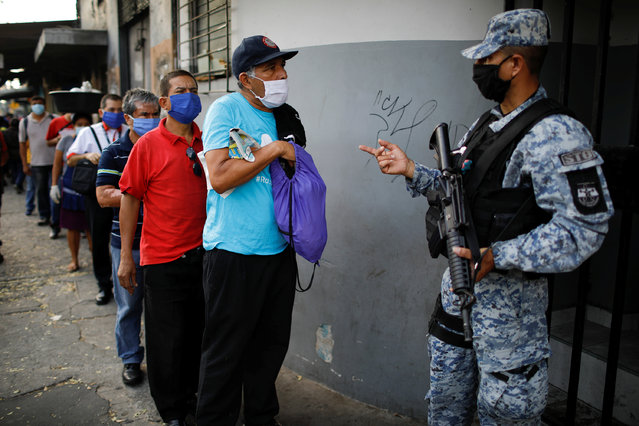 A policeman asks for documents in a checkpoint during a police and army joint operation as part of security measures to keep people out of city downtown markets during a quarantine throughout the country to curb the spread of the coronavirus disease (COVID-19), in San Salvador, El Salvador on April 20, 2020. (Photo by Jose Cabezas/Reuters)
