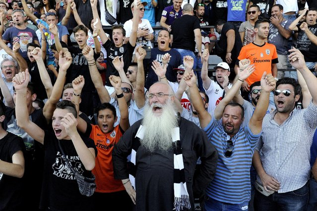 PAOK fans, among them a Greek Orthodox priest (C), cheer for Bulgarian forward Dimitar Berbatov (not pictured) during his presentation at the Toumba Stadium in Thessaloniki, Greece, September 3, 2015. Berbatov was treated to a hero's welcome on Thursday as 10,000 jubilant PAOK Salonika fans turned up to greet the club's new signing at their Toumba Stadium. (Photo by Alexandros Avramidis/Reuters)