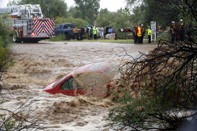 Water washes over the car after the driver was rescued by members of Northwest Fire District north of Tucson, Ariz., on Monday, September 8, 2014. The Phoenix and Tucson metro areas were hit by heavy rains, causing flooding and damage. More than 3 inches of rain closed parts of several Phoenix freeways. In Tucson, the National Weather Service recorded nearly 2 inches of rain. (Photo by Ron Medvescek/AP Photo/Arizona Daily Star)