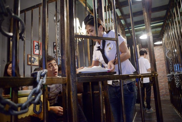 "This picture taken on September 9, 2014 shows a waiteress handing over food to customers at a prison themed restaurant in Tianjin. As more themed restaurants are popular in China, a ""prison style"" restaurent in Tianjin is aimed at reminding people to observe the law and to be good citizens. (Photo by Wang Zhao/AFP Photo)"