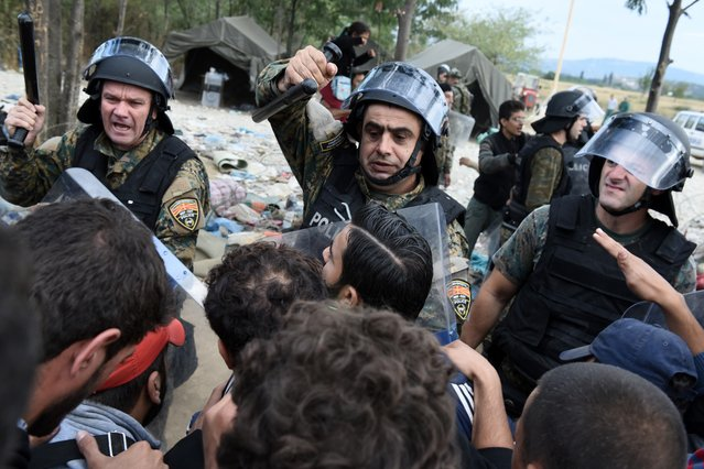 Macedonian policemen scuffle with refugees and migrants as they wait to pass the borders from the northern Greek village of Idomeni, to southern Macedonia, Monday, September 7, 2015. The country has borne the brunt of a massive refugee and migration flow of people heading into the European Union. (Photo by Giannis Papanikos/AP Photo)