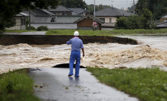 People look at flood waters from the Kinugawa river (R) caused by typhoon Etau at a residential area in Joso, Ibaraki prefecture, Japan, September 10, 2015. (Photo by Issei Kato/Reuters)