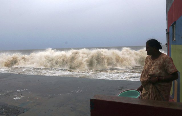A woman watches waves splash on shores of the Arabian Sea in Mumbai, India, Wednesday, June 3, 2020. A storm in the Arabian Sea off India's west coast intensified into a severe cyclone on Wednesday, gathering speed as it barreled toward India's financial capital of Mumbai. Nisarga was forecast to drop heavy rains and winds gusting up to 120 kilometers (75 miles) per hour when it makes landfall Wednesday afternoon as a category 4 cyclone near the coastal city of Alibagh, about 98 kilometers (60 miles) south of Mumbai, India's Meteorological Department said. (Photo by Rafiq Maqbool/AP Photo)