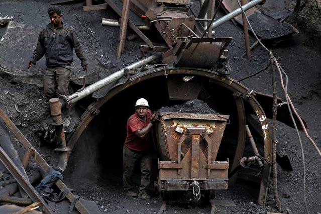 In this Monday, Aug. 18, 2014 photo, an Iranian coal miner pushes a metal cart loaded with coal at a mine near the city of Zirab 212 kilometers (132 miles) northeast of the capital Tehran, on a mountain in Mazandaran province, Iran. The miner move up to 100 tons of coal a day. (Photo by Ebrahim Noroozi/AP Photo)