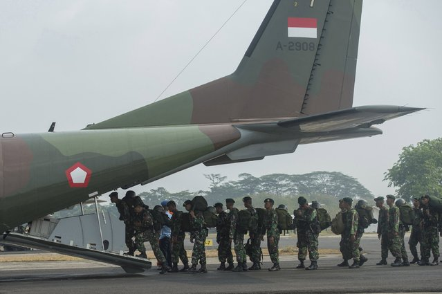 Indonesian soldiers from the Army Strategic Reserve Command board a military plane on their way to assist in fire fighting in Riau province, Sumatra Island at Halim Air Force Base, Jakarta September 15, 2015 in this photo taken by Antara Foto. (Photo by Widodo S. Yusuf/Reuters/Antara Foto)