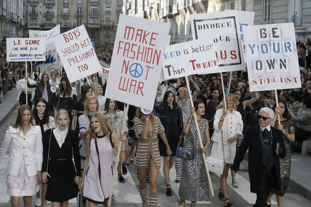 German designer Karl Lagerfeld (R) appears with models who stage a demonstration at the end of his Spring/Summer 2015 women's ready-to-wear collection for French fashion house Chanel during Paris Fashion Week September 30, 2014. Karl Lagerfeld created an immense Boulevard Chanel for his fashion show on Tuesday, even staging a street demonstration by fashionably dressed models for Spring/Summer 2015. (Photo by Gonzalo Fuentes/Reuters)