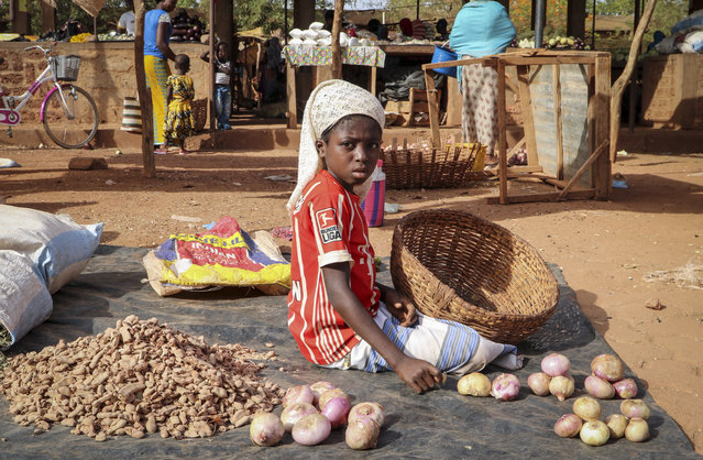In this Wednesday, May 13, 2020, photo, a child sits on the ground selling onions at a market stall in Tougan, Burkina Faso. Violence linked to Islamic extremists has spread to Burkina Faso's breadbasket region, pushing thousands of people toward hunger and threatening to cut off food aid for millions more. (Photo by Sam Mednick/AP Photo)