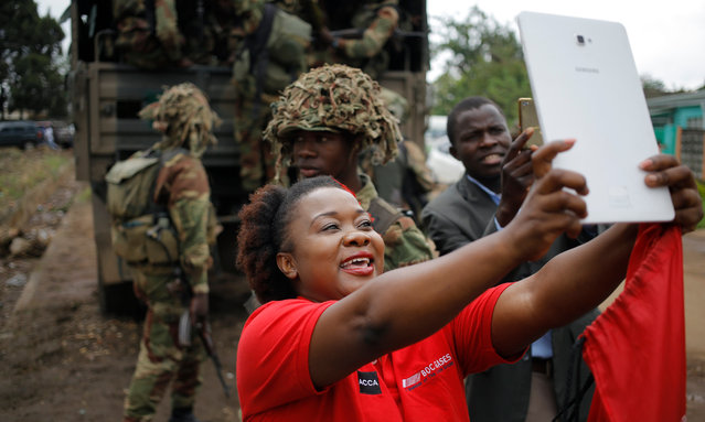 A women does a selfie with soldiers at an anti President Mugabe rally held by the War Veterans as part mass action protests that have brought the city to a stand still in Harare, Zimbabwe, 18 November 2017. The Zimbabwe National Army (ZNA) has taken over the control of the running of the country with Robert Mugabe, being under house arrest for days, but making his first public appearance at a University graduation ceremony on 17 November 2017. (Photo by Kim Ludbroo/EPA/EFE)