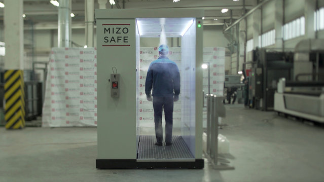 An employee walks through a disinfection tunnel manufactured by Russian company Mizotty at the company's factory in Penza, Russia on June 17, 2020, in this still image taken from undated handout video. (Photo by Mizotty/Reuters TV via Reuters)