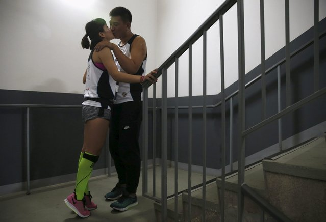 A couple kisses during a vertical run event at China World Summit Wing hotel in Beijing, China, September 19, 2015. (Photo by Kim Kyung-Hoon/Reuters)