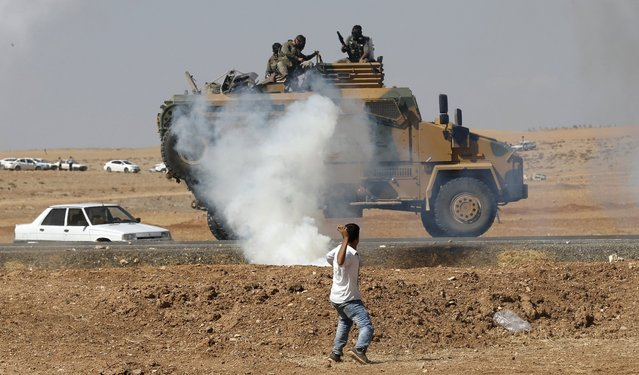 A protester throws stones at an armoured army vehicle during a pro-Kurdish demonstration in solidarity with people of Kobani, near the Mursitpinar border crossing on the Turkish-Syrian border, in the Turkish town of Suruc in southeastern Sanliurfa province October 7, 2014. Islamic State fighters advanced into the south west of the Syrian Kurdish town of Kobani overnight, a monitoring group said on Tuesday, taking several buildings to gain attacking positions from two sides of the city. (Photo by Umit Bektas/Reuters)