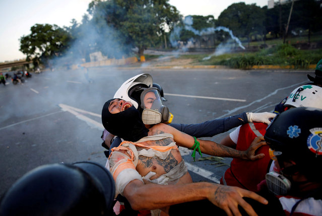 """An injured opposition supporter is helped by volunteer members of a primary care response team during clashes with riot security forces at a rally against Venezuelan President Nicolas Maduro's government in Caracas, Venezuela, June 22, 2017. Ivan Alvarado: """"This image was taken next to an airforce base where another protestor was fatally injured that day. I don't know how this man was injured, I first saw him as the first aid volunteers carried him out from the midst of the tear gas. You can really see the pain in his expression as he cries out. After I took the image the motorbike speeded off down the highway"""". (Photo by Ivan Alvarado/Reuters)"""