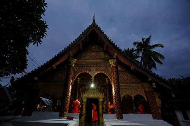 Buddhist monks prepare to collect alms before sunrise at Wat Sibounheuang temple in Luang Prabang, Laos July 31, 2016. (Photo by Jorge Silva/Reuters)