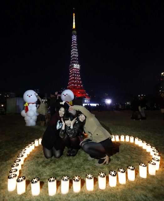 People take a picture in front of Tokyo Tower which is illuminated to celebrate the New Year, after a countdown event early Tuesday morning. (Photo by Japan Today)