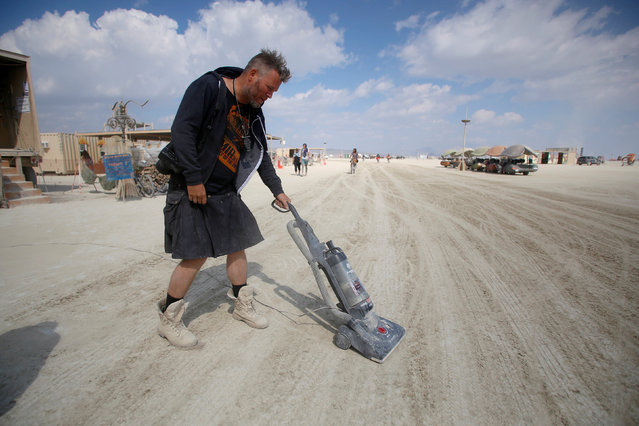 Huybert Van De Stadt vacuums the Playa as approximately 70,000 people from all over the world gathered for the 30th annual Burning Man arts and music festival in the Black Rock Desert of Nevada, U.S. September 4, 2016. (Photo by Jim Urquhart/Reuters)