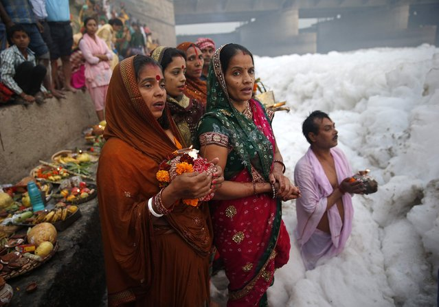 Hindu women worship the Sun god Surya in the polluted waters of the river Yamuna during the Hindu religious festival of Chatt Puja in New Delhi October 30, 2014. (Photo by Ahmad Masood/Reuters)