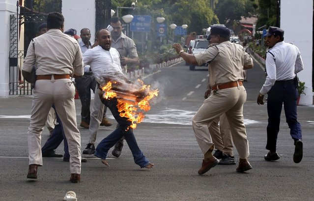 Manoj Tripathi, of the Nationalist Congress Party (NCP), sets himself on fire as police officers try to detain him, at the gates of Raj Bhawan in Bhopal, India, 07 September 2016. The NCP leader, who has been detained by the police, was demanding the arrest of the outgoing governor Ram Naresh Yadav for his alleged involvement in an admission and recruitment racket in Vyapam, known as the Vyapam scam. (Photo by Sanjeev Gupta/EPA)