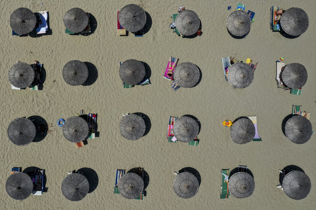 This aerial view taken on July 6, 2019, shows parasols on a beach of the Adriatic Sea in Durres, as a heatwave sweeps through Europe. Temperatures rise to 39 degrees Celsius in Albania. (Photo by Gent Shkullaku/AFP Photo)