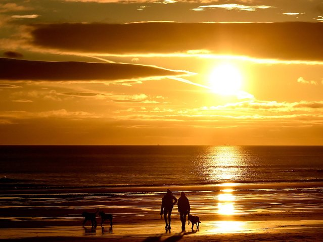 Dog walkers during sunrise on Longsands beach in Tynemouth, UK, on October 23, 2014. (Photo by Owen Humphreys/PA Wire)